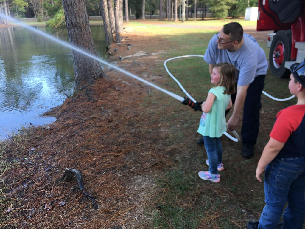 Firefighter Coty Leard showing a future firefighter all about hose handling.