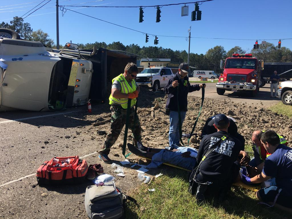 Assistant Chief Wesley Perry, Captain Ryan Kuhn, and firefighters Tyler Lawrence, Hunter Windom, Albert Long, and Sean Smith treat the injuries of the driver and prepare him for transport to the hospital.