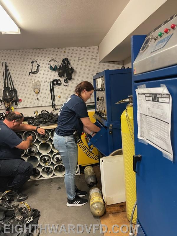 FF-2/EMT Ted Mocklin assisting Elizabeth Crawford in filling SCBA cylinders.